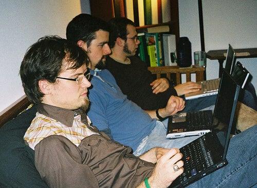 yan yana oturmuş bilgisayara bakan üç adam