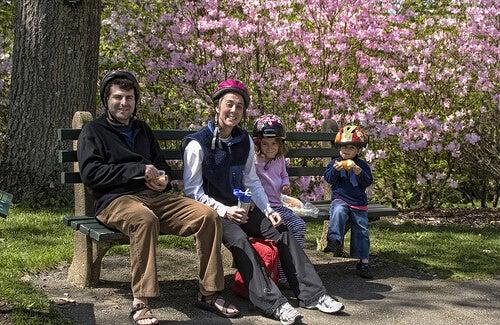 bisiklet kasklarıyla bankta oturan baba çocuklar