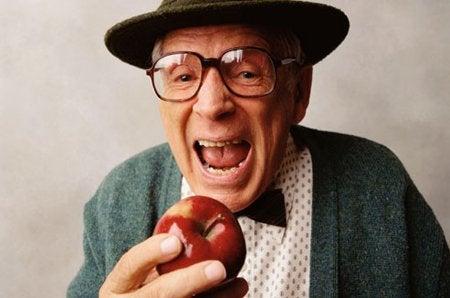 elmayı ısırmak üzere olan yaşlı şapkalı gözlüklü adam