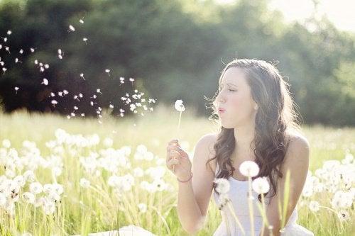 karahindiba çiçeğine üfleyen kadın