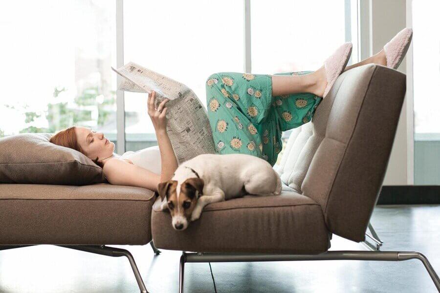 uzanarak gazete okuyan kadın ve köpeği