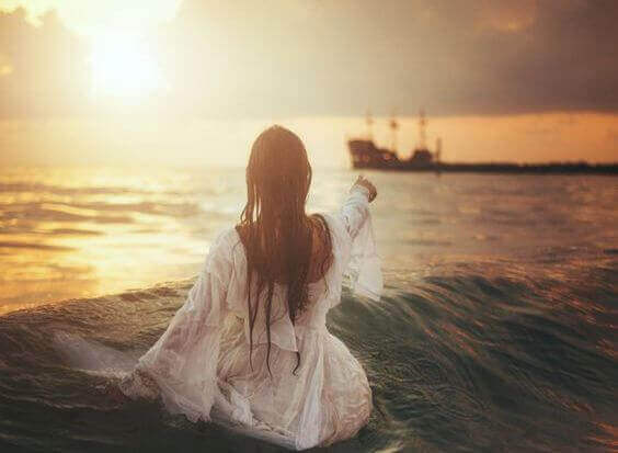 denizde beyaz elbiseli kadın