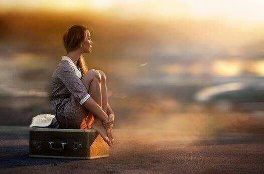 kendini yalnız hisseden kadın bavulun üzerinde oturuyor
