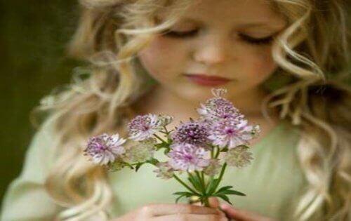 elinde çiçek olan kız çocuğu