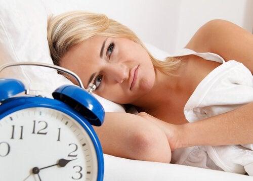 uyku problemi yaşayan sarışın kadın ve mavi çalar saat
