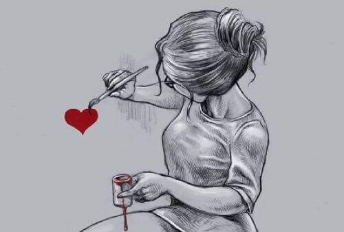 duvara kırmızı kalp çizen siyah beyaz kadın