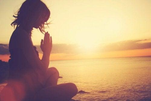 deniz kenarında dua eden kadın