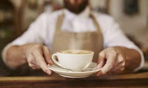 bir fincan kahve uzatan barista