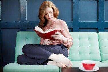 koltukta kitap okuyup kahve içen kadın