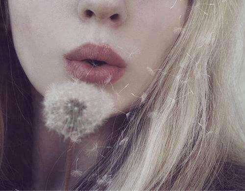 karahindiba çiçeği üfleyen kadın