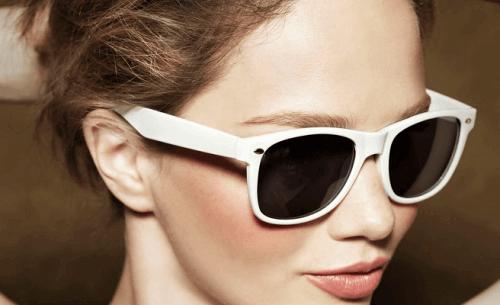 beyaz çerçeveli güneş gözlüğü takmış kadın