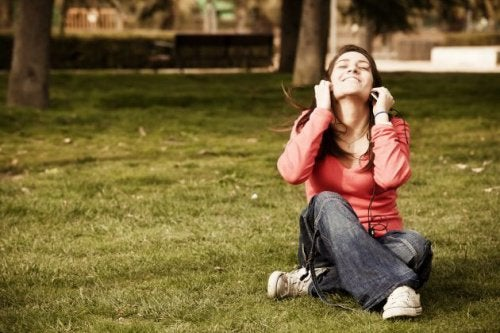 çimde oturarak müzik dinleyen kadın