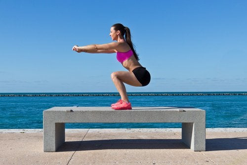 deniz kenarında bankın üstünde squat yapan kadın