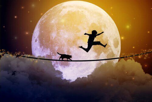 ay ışığında kediyle cambazlık yapan çocuk
