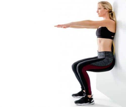dizleri güçlendirmek için duvara dayanıp kolları uzatarak çömelmek