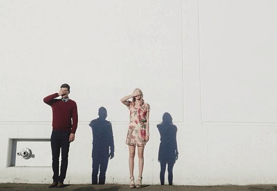 gözlerini kapatmış duvarın önünde duran kadın ve erkek