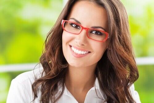 kırmızı çerçeveli gözlüklü gülümseyen kadın