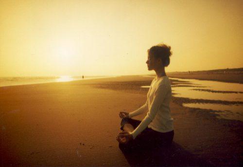 gün batımı sahilde meditasyon yapan kadın