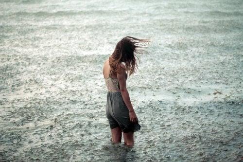 yağmur altında nehirde yürüyen yalnız kadın