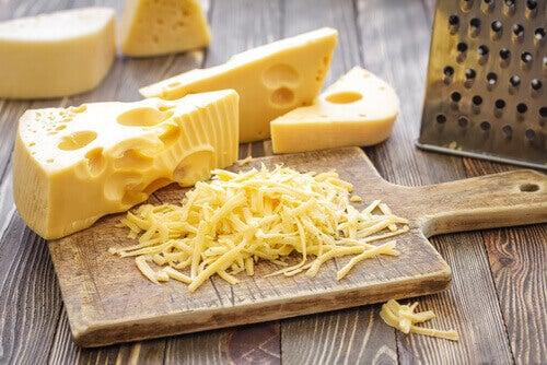 kesme tahtasının üstünde üçgen dilim ve rendelenmiş peynir