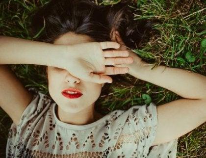 çimlerde uzanmış gözleri kapalı kadın