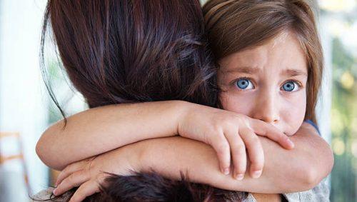 annesine sarılan korkmuş çocuk