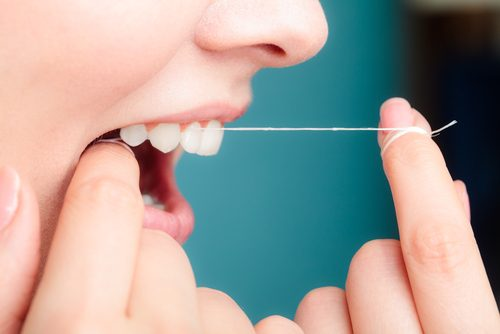 diş ipini tutan eller ve açık ağız