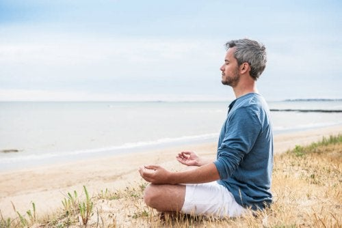 deniz kenarında meditasyon yapan adam