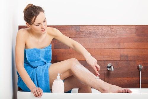 banyoda bacaklarını tıraş eden kadın