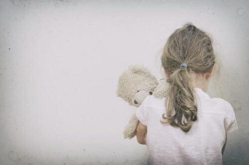 oyuncağına sarılan yalnız kız çocuğu