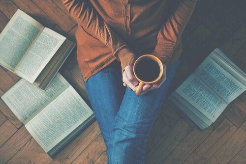 elinde kahvesi olan kişi kitaplarla