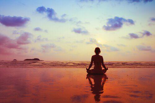 sahilde meditasyon yapan kadın