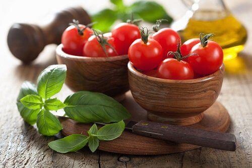 kaselerin içinde minik kırmızı domatesler ve fesleğen