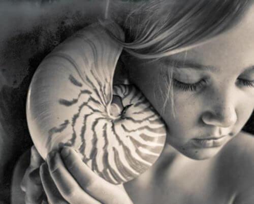 deniz kabuğunu dinleyen kız