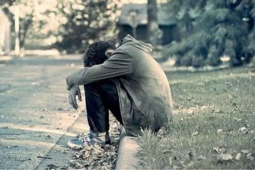 yol kenarında oturan yalnız çocuk
