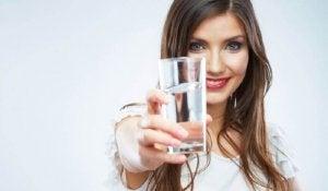 elinde bir bardak su tutan kadın