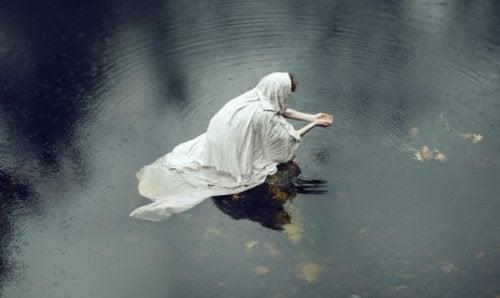 gölde çömelmiş yalnız kadın