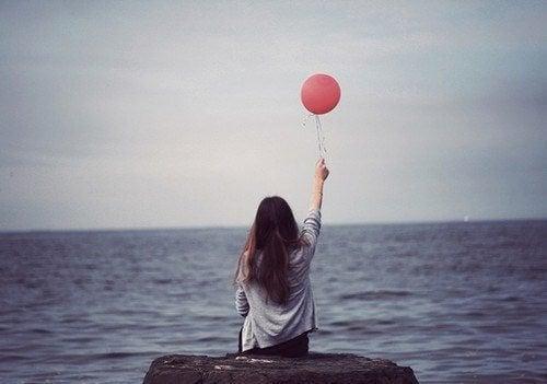 sahil kenarında balon tutarak oturan kız
