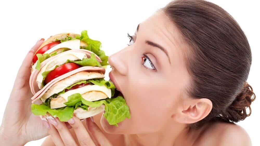 kocaman bir sandviç yiyen kadın