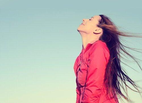 açık havada rüzgara karşı gülümseyen kadın