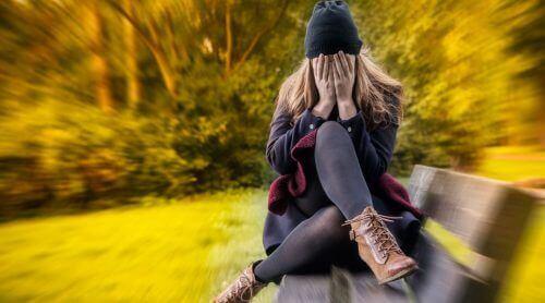 bankta oturan hüzünlü kadın