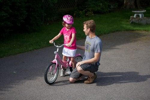 kızına bisiklet öğreten baba