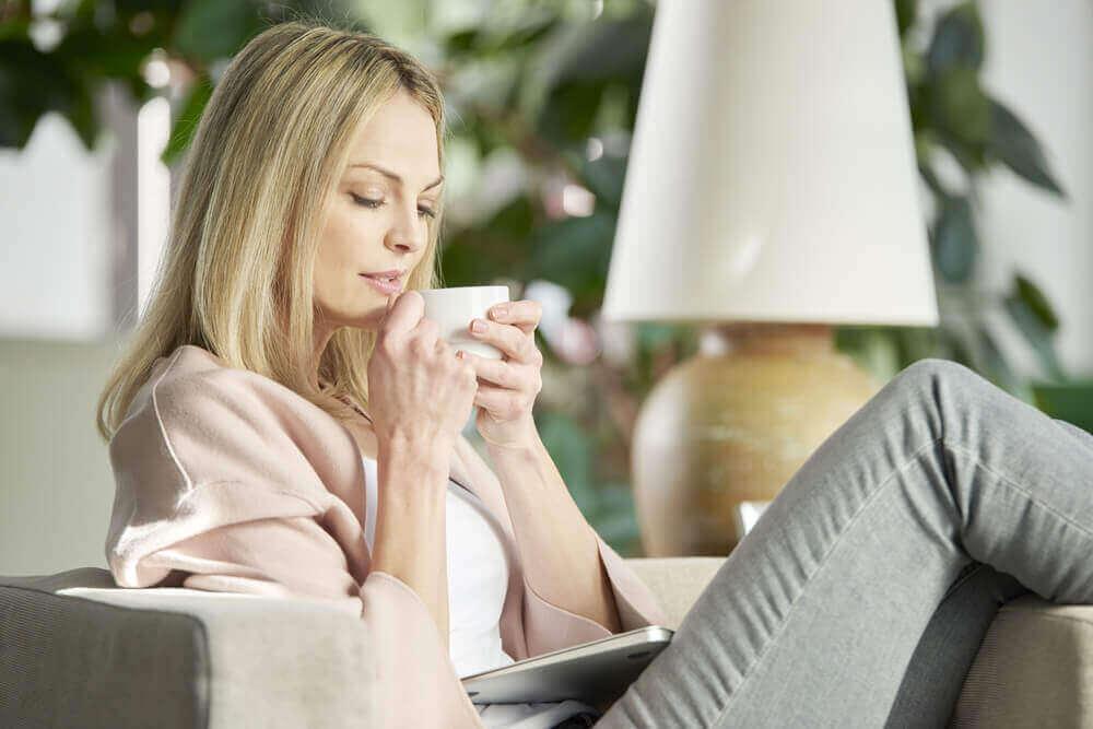 baş ağrısını hafifletmek için çay içen kadın