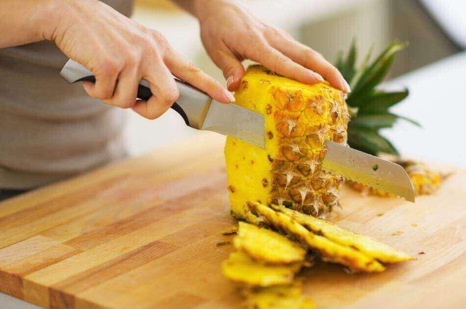 ananasın kabukları bıçakla kesilirken