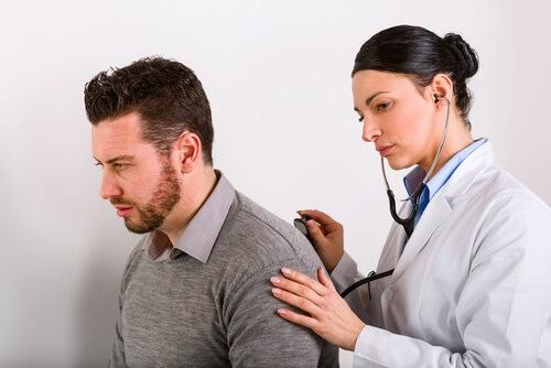 hastanın sırtını dinleyen kadın doktor