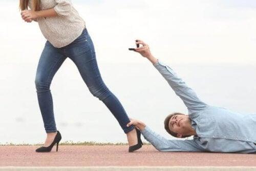 kadının ayağına yapışan ve elinde yüzük tutan erkek