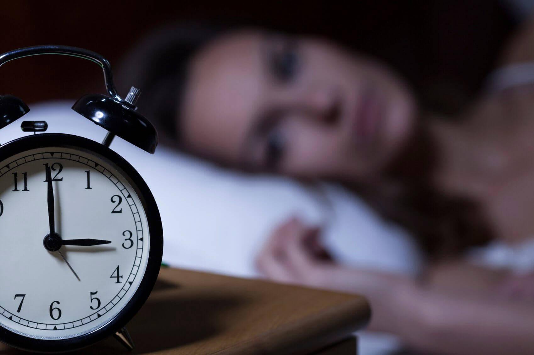 saat yatakta yatan kadın uykusuzluk