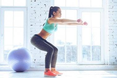 ağırlıklı squat yapan kadın
