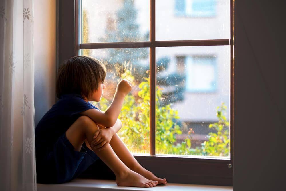 camdan dışarı bakan hüzünlü çocuk