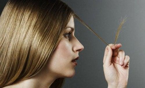 saç uçlarını inceleyen kadın